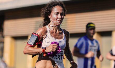 Žena při běhu využívá běžecké aplikace v mobilním telefonu.
