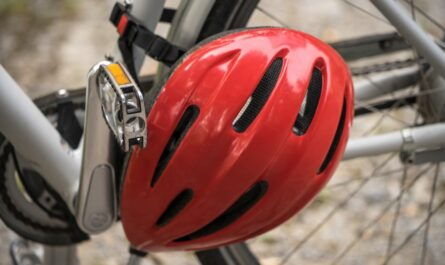Červená cyklistická helma pověšená na jízdním kole.